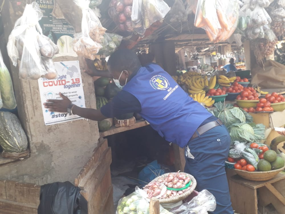 Blog 7 Henry pinning up posters in the market
